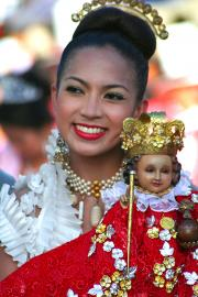A Sinulog Dancer carrying a statute of the Santo Nino