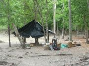 Our Muleteer unpacks camp at the base of an unexcavated Mayan structure.