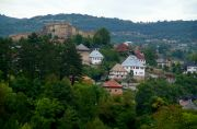 The view of the old Jajce with the fortress on the hill and a couple of houses in traditional style.