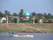 The river with a mosque on the other side of the river bank.