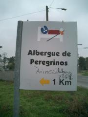 Announcement of a shelter for pilgrims with the yellow arrow