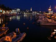 Split's fishing harbour at night, a couple of ferries leave from the same waterfront.