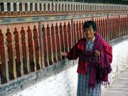 Woman spinning prayers wheels at Changangka Dzong