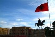 Albanian flag flying by the side of the monument of the Albanian hero, Skanderbeg.