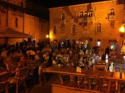 The John Paul II Square at night with the Corte's bar and tables.