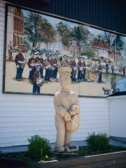 A wooden Truro monument with a mural in background